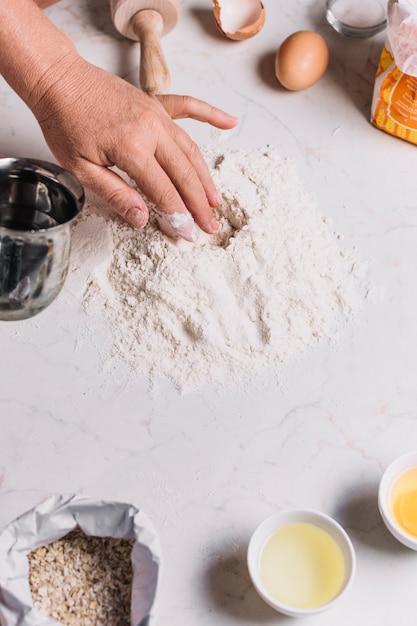 Close-up, de, um, baker's, mão, com, vário, assando ingredientes, ligado, contador cozinha Foto gratuita