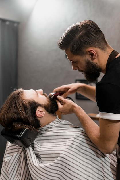 Close-up, de, um, barbeiro, aparando, barba homem, com, elétrico, aparador Foto gratuita