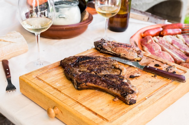 Close-up, de, um, carne cozida, e, faca, ligado, tábua madeira, tábua cortante Foto gratuita