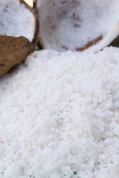 Close-up de um coco e uma pilha de coco ralado Foto Premium
