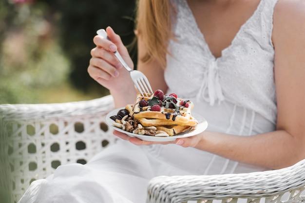 Close-up, de, um, comer mulher, waffle, ligado, café manhã Foto gratuita