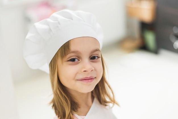 Close-up, de, um, cute, menina sorridente, desgastar, chapéu cozinheiro Foto gratuita