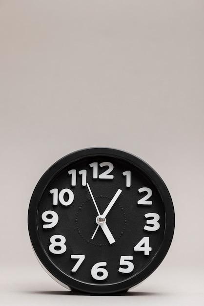 Close-up de um despertador preto no fundo liso Foto gratuita