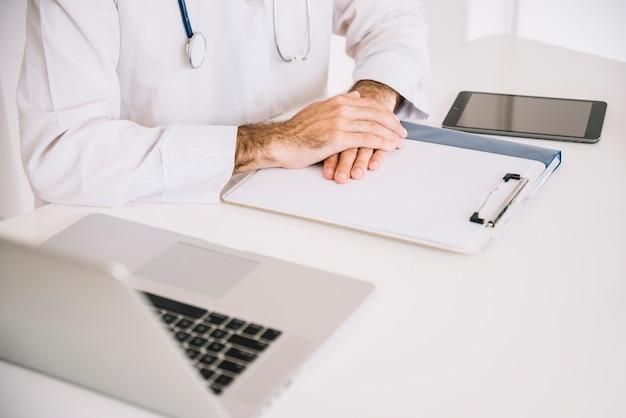 Close-up, de, um, doutor masculino, mão, ligado, área de transferência, com, laptop, escrivaninha Foto gratuita