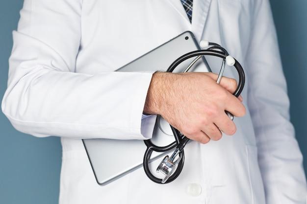 Close-up, de, um, doutor masculino, mão, segurando, tablete digital, e, estetoscópio Foto gratuita