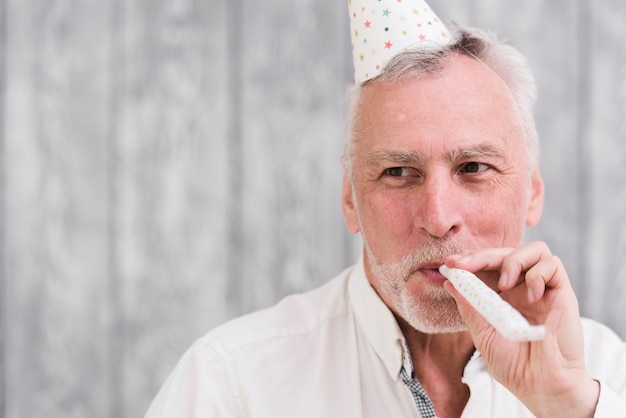 Close-up, de, um, feliz, homem ancião, soprar, soprador partido Foto gratuita