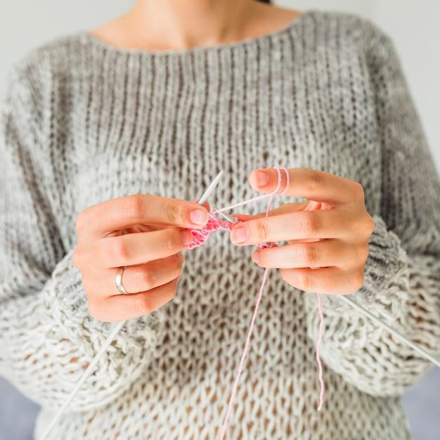 Close-up, de, um, female's, mão, crocheting, com, cor-de-rosa, fio Foto gratuita