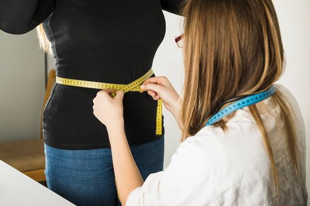 Close-up, de, um, femininas, dietician, medindo, paciente, barriga, em, clínica Foto gratuita