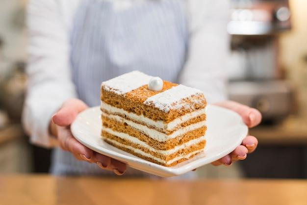 Close-up, de, um, femininas, padeiro, servindo, fatia pastelaria, em, a, branca, forma coração, prato Foto gratuita