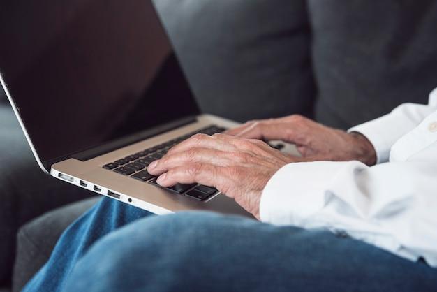 Close-up, de, um, homem idoso, mão, digitando, ligado, laptop Foto gratuita