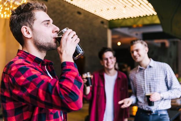 Close-up, de, um, homem jovem, bebendo cerveja, em, bar, restaurante Foto gratuita