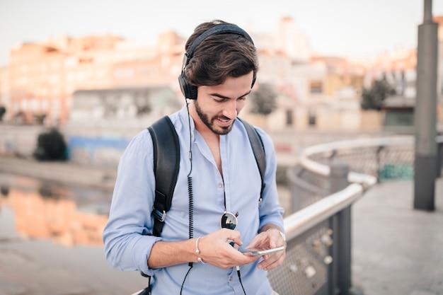 Close-up, de, um, homem jovem, escutar música, ligado, smartphone Foto gratuita