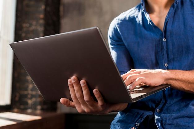 Close-up, de, um, homem jovem, usando computador portátil, em, mão Foto gratuita