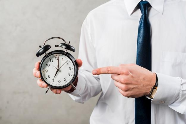 Close-up, de, um, homem negócios, apontar dedo, a, tempo, contra, parede cinza Foto gratuita
