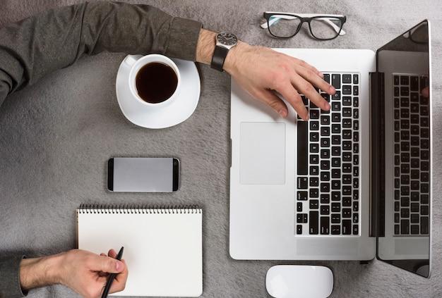 Close-up, de, um, homem negócios, escrita, ligado, área de transferência, usando, tablete digital, escrivaninha Foto gratuita
