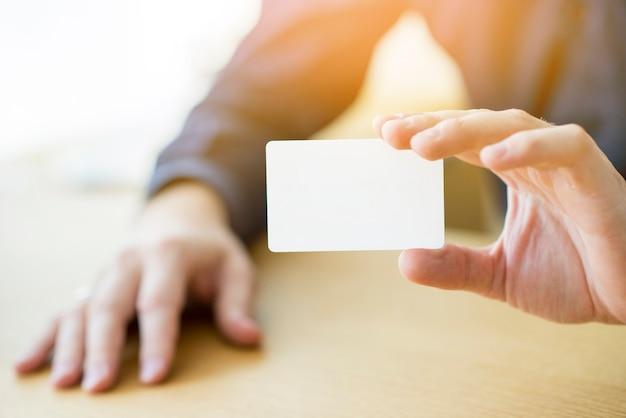 Close-up, de, um, homem negócios, mão, segurando, em branco, cartão branco Foto gratuita