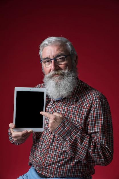 Close-up, de, um, homem sênior, óculos desgastando, mostrando, tablete digital, contra, experiência vermelha Foto gratuita