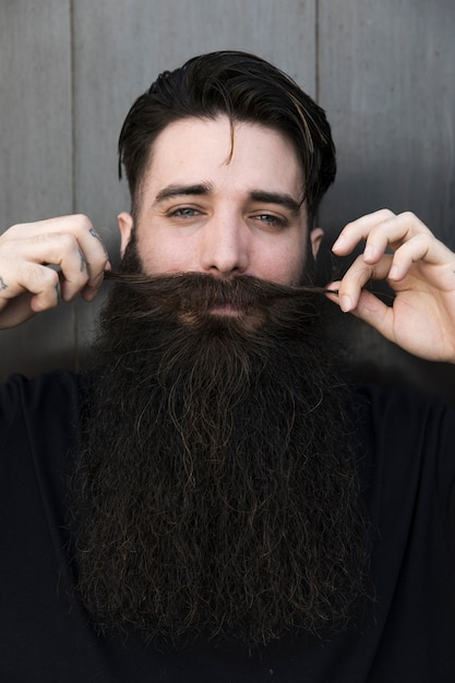 Close-up, de, um, homem sorridente, puxando, seu, bigode Foto gratuita