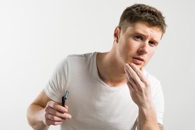 Close-up, de, um, homem, tocar, seu, pele, após, barbear, segurando, navalha, mão, contra, fundo branco Foto gratuita