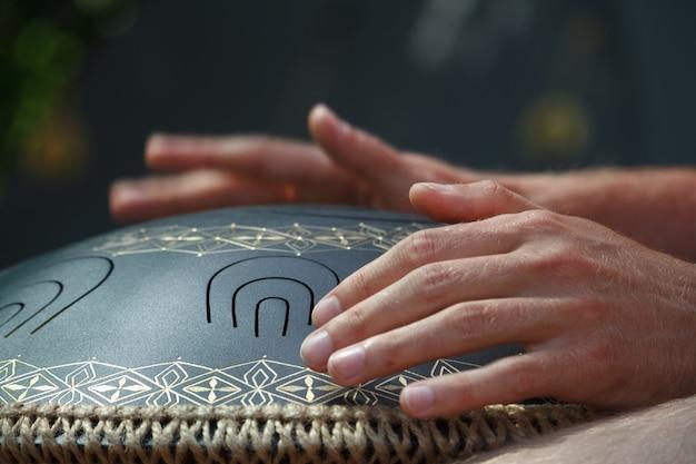 Close-up, de, um, homens, mão, tocando, ligado, modernos, musical, instrumento mão, panela, ou, vadjraghanta, ou, metal, língua, drumon, foco seletivo Foto Premium
