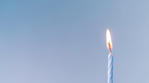 Close-up, de, um, iluminado, vela, contra, experiência azul Foto gratuita