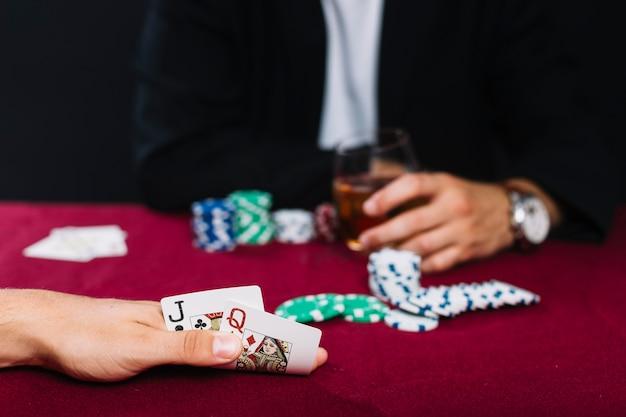 Close-up, de, um, jogador, passe, com, cartão jogando, ligado, vermelho, pôquer, tabela Foto gratuita