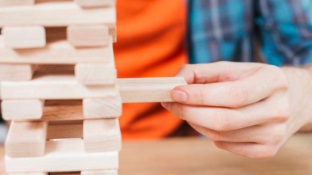 Close-up, de, um, jogo homem, blocos de madeira, torre, jogo Foto gratuita