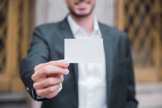 Close-up, de, um, jovem, homem negócios, mostrando, branca, cartão visita, frente, câmera Foto gratuita