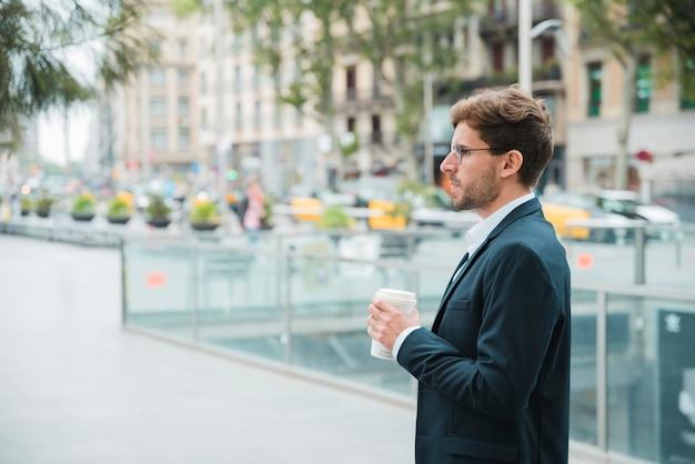 Close-up, de, um, jovem, homem negócios, segurando, copo café descartável, em, mão, levantando rua Foto gratuita