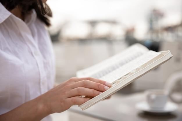 Close up de um livro em mãos femininas Foto gratuita