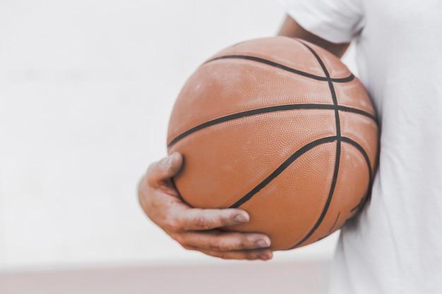 Close-up, de, um, macho, jogador, segurando, basquetebol Foto gratuita