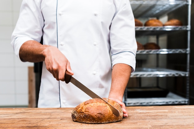Close-up, de, um, macho, padeiro, corte, a, pão, com, faca afiada Foto gratuita