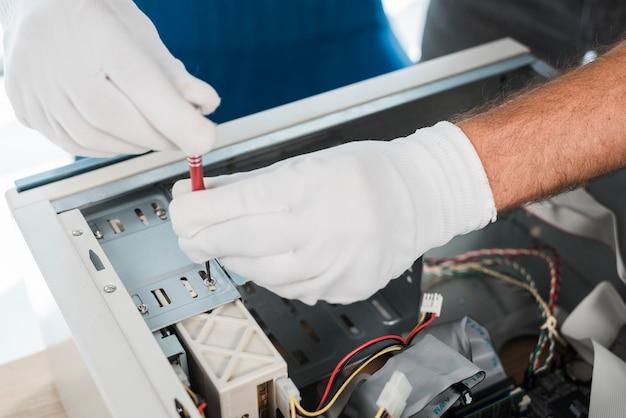 Close-up, de, um, macho, técnico, mão, desgastar, luvas, reparar, computador Foto gratuita