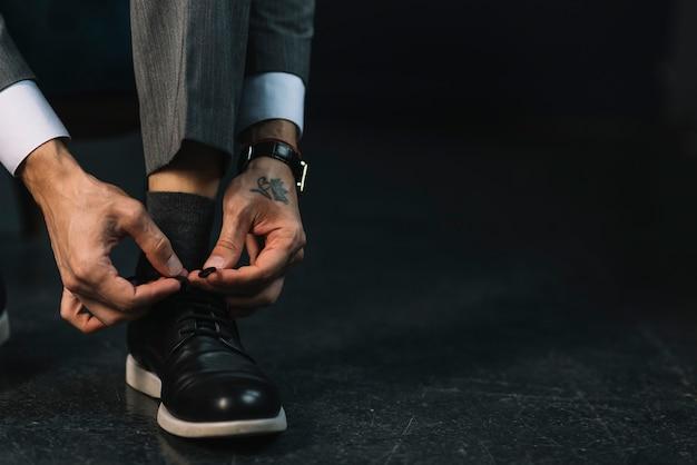 Close-up, de, um, mão homem, amarrando, cadarço Foto gratuita