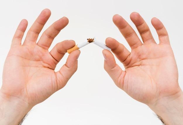 Close-up, de, um, mão homem, quebrar, a, cigarro, contra, fundo branco Foto gratuita