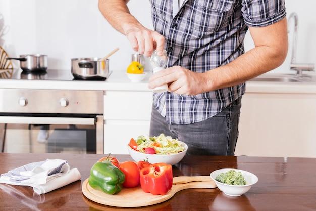 Close-up, de, um, mão homem, temperando, salada, com, fresco, mar sal, em, a, cozinha Foto gratuita