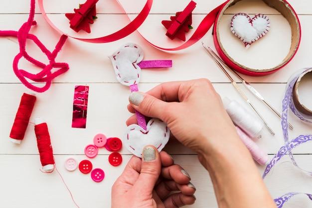 Close-up, de, um, mão mulher, fazer, a, branca, corações, branco, tabela Foto gratuita