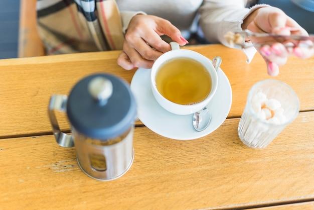 Close-up, de, um, mão mulher, pôr, açúcar marrom, com, tong, em, a, chá herbário, ligado, tabela madeira Foto gratuita