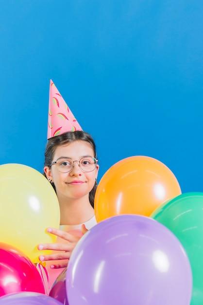 Close-up, de, um, menina, com, balões coloridos, ligado, azul, fundo Foto gratuita