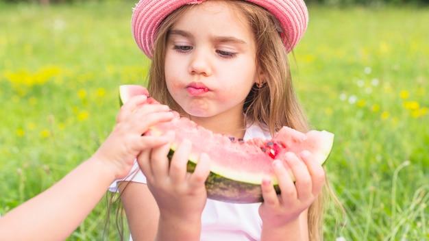 Close-up, de, um, menina, comer, melancia, parque Foto gratuita