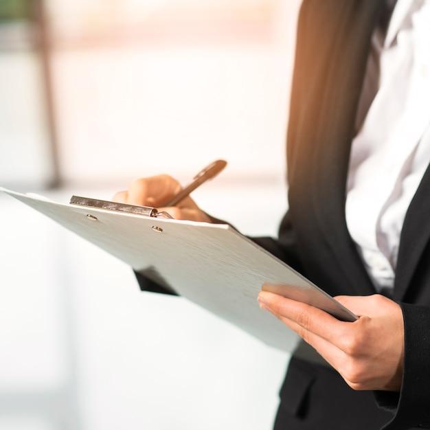 Close-up, de, um, mulher, escrita, ligado, área de transferência, com, caneta Foto gratuita