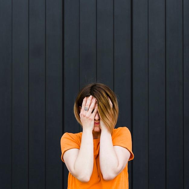 Close-up, de, um, mulher jovem, ficar, contra, parede preta, cobertura, dela, rosto, com, mãos Foto gratuita
