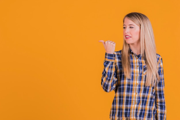 Close-up, de, um, mulher jovem, mostrando, polegar, gesto, para, lado, contra, um, laranja, fundo Foto gratuita