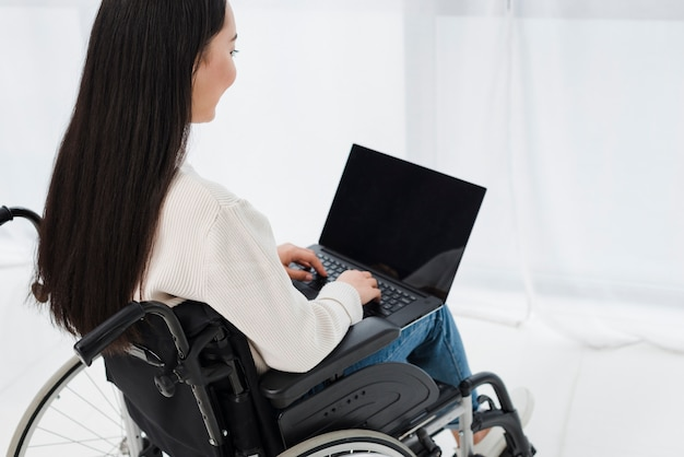 Close-up, de, um, mulher jovem, sentando, ligado, cadeira rodas, usando computador portátil Foto gratuita