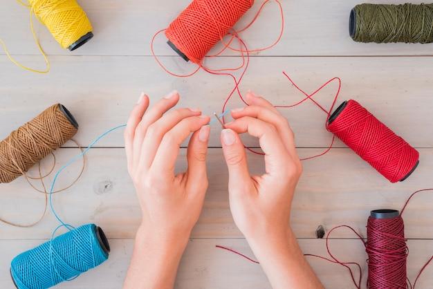 Close-up, de, um, mulher, mão, inserindo, azul, yarn, em, agulha, ligado, tabela madeira Foto gratuita