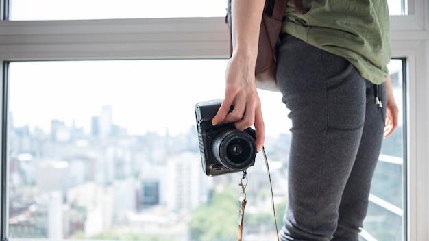 Close-up, de, um, mulher segura, câmera, ficar, perto, janela Foto gratuita