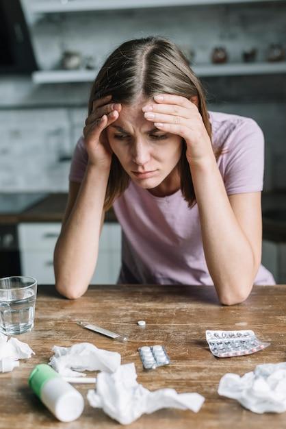 Close-up, de, um, mulher, sofrimento, de, febre, com, medicamentos, e, amarrotado, papel tecido, ligado, escrivaninha madeira Foto gratuita