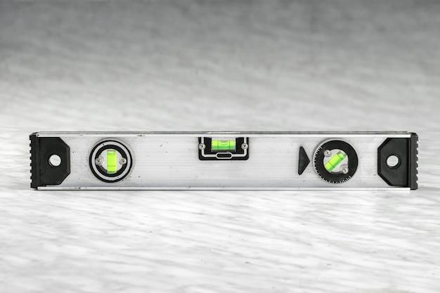 Close-up de um nível de metal de construção, uma régua deitada nas placas. Foto Premium