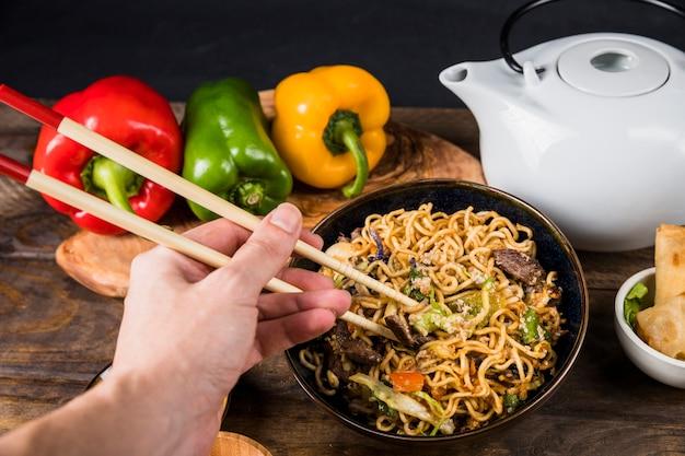 Close-up, de, um, pessoa, comer, a, amigo, udon, noodles, com, chopsticks Foto gratuita