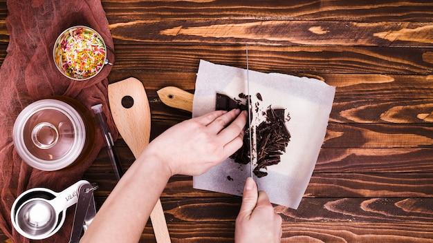 Close-up, de, um, pessoa, corte barra chocolate, com, faca, ligado, papel, sobre, a, tabela madeira Foto gratuita